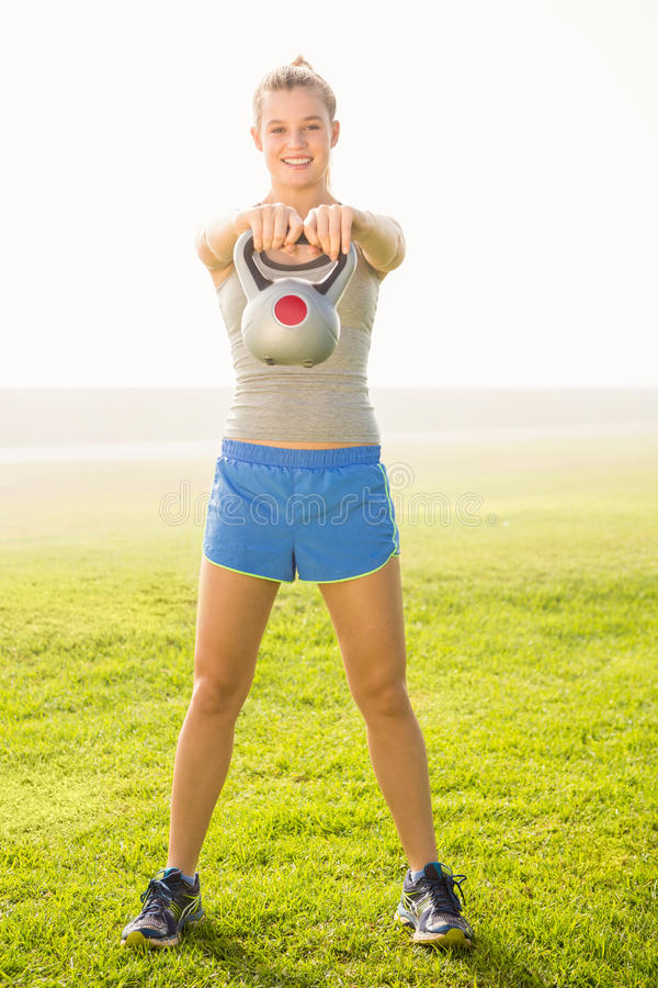 Smiling sporty blonde exercising with kettlebell stock photo