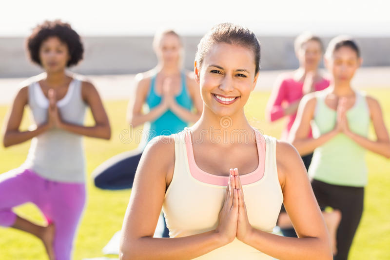 Smiling sporty brunette doing yoga in yoga class. Portrait of smiling sporty brunette doing yoga in yoga class in parkland royalty free stock photos