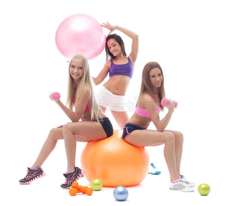 Smiling sporty girls posing with fitness items. Smiling young sporty girls posing with fitness items royalty free stock photos