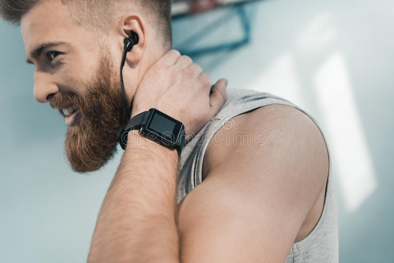 Smiling sporty man with smartwatch on wrist. Portrait of smiling sporty man with smartwatch on wrist royalty free stock image
