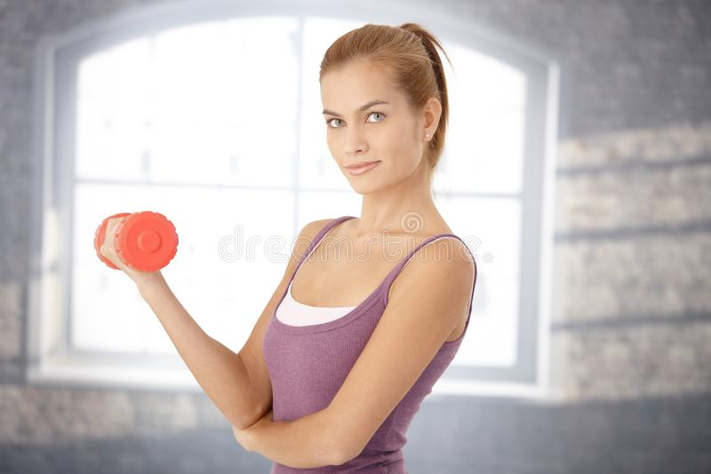 Smiling sporty woman with dumbbell royalty free stock photo