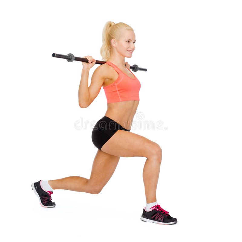 Smiling sporty woman exercising with barbell stock photography