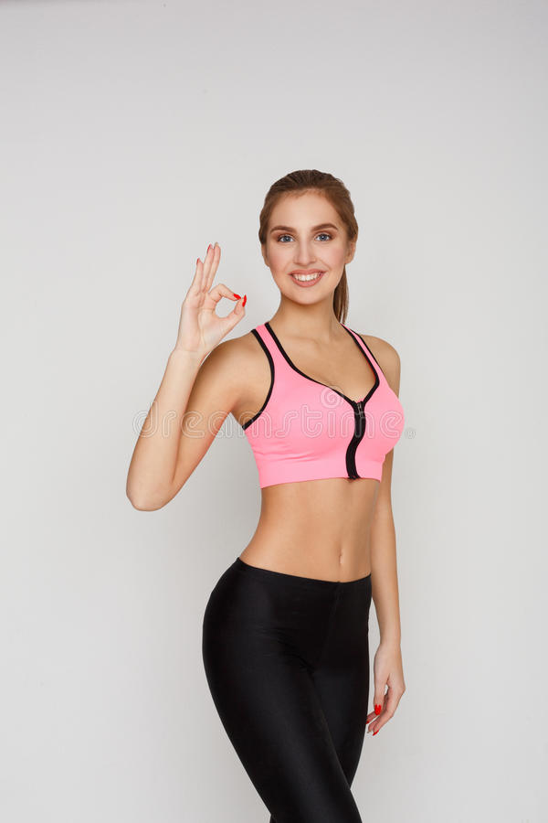 Smiling sporty woman gesturing ok sign royalty free stock image