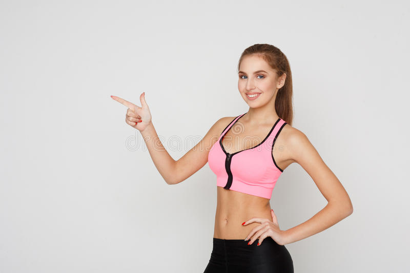 Smiling sporty woman point away royalty free stock photo
