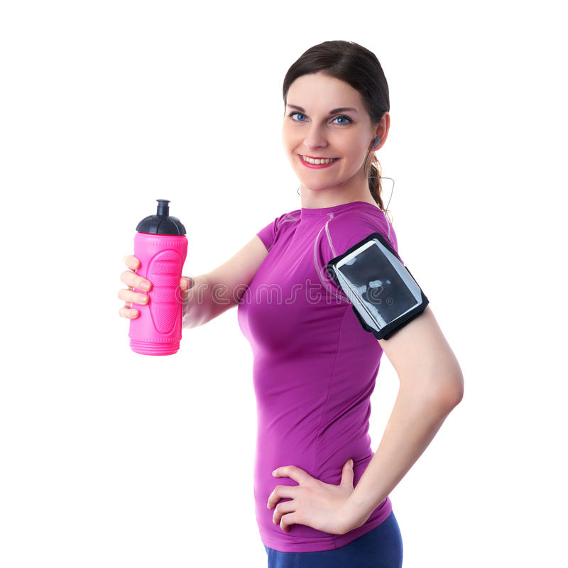 Smiling sporty woman in violet T-short over white isolated background. Smiling sporty woman in violet T-short with pink drinking bottle, smart phone device and stock image