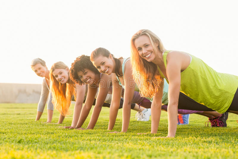 Smiling sporty women doing push ups during fitness class stock images