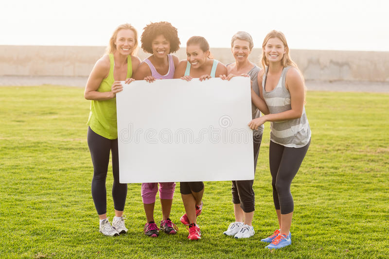 Smiling sporty women holding poster with copy space. Portrait of smiling sporty women holding poster with copy space in parkland royalty free stock image