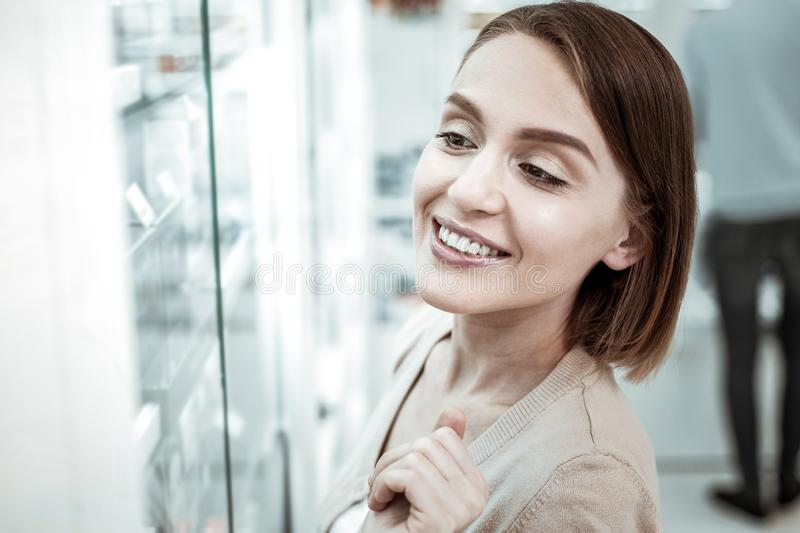A smiling spouse deciding to buy extra vitamins while her husband at checkout. Buying extra vitamins. A smiling beautiful spouse deciding to buy extra vitamins royalty free stock photography