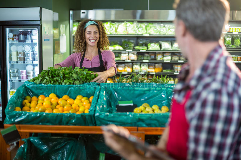 Smiling staffs interacting with each other in organic section. Of supermarket stock photography