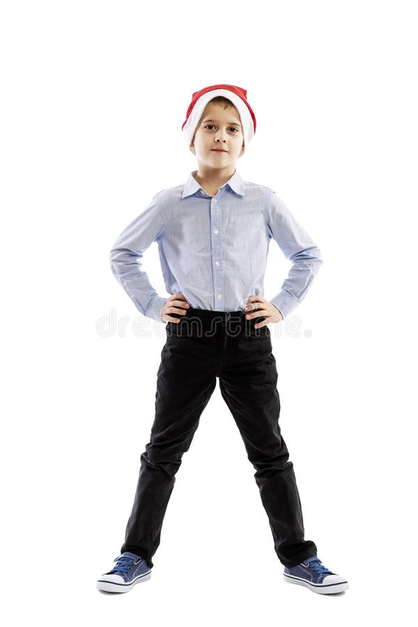 Smiling standing schoolboy in santa claus hat. Full height. Christmas mood. Isolated over white background. royalty free stock image