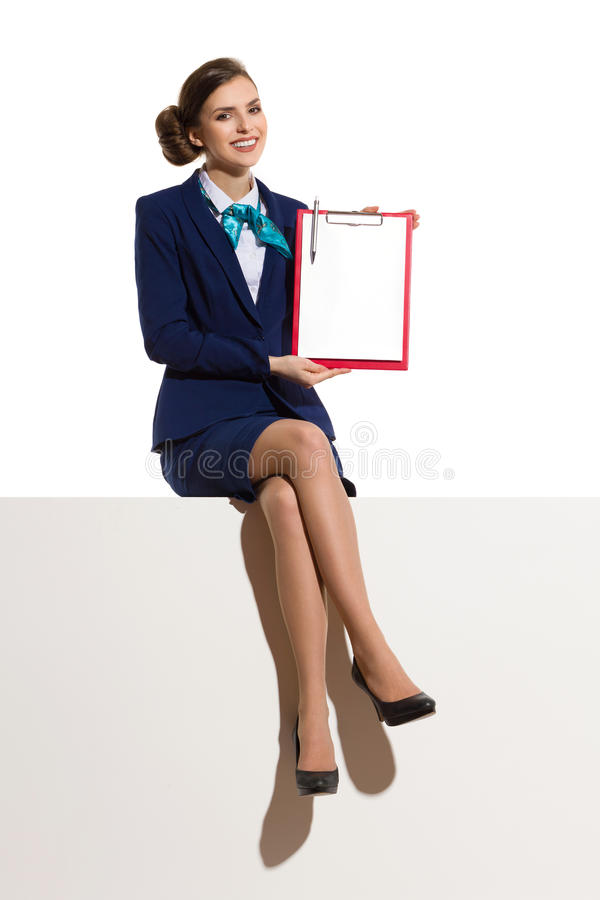 Smiling Stewardess Sitting On A Top And Showing Clipboard royalty free stock photos
