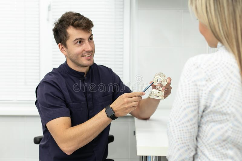 Smiling stomatologist holds pointing at model of jaw and talking with blond woman. Selective focus.  royalty free stock images