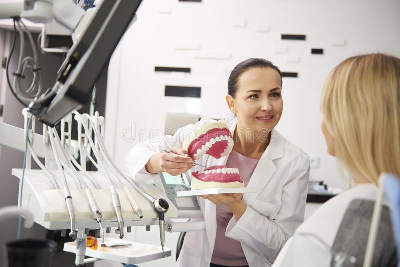 Stomatologist and woman holding a conversation in dentist`s clinic. Smiling stomatologist and women holding a conversation in dentist`s clinic royalty free stock photography