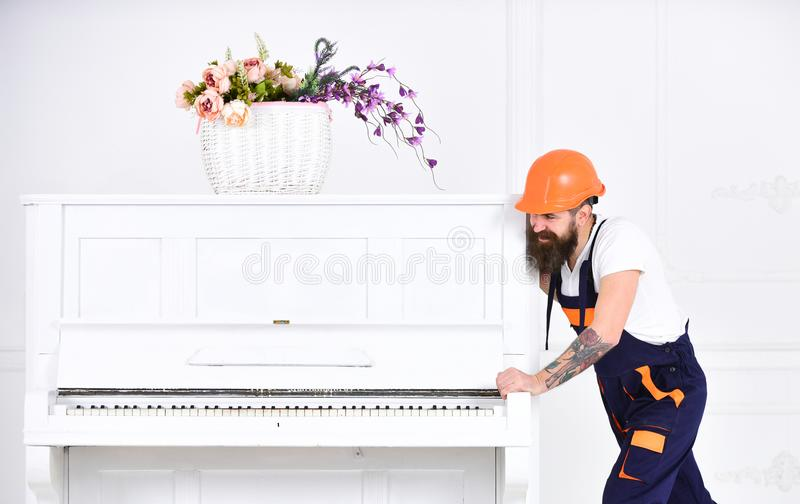 Smiling strong man with stylish beard and mustache trying to move old wooden piano with flower vase. Handsome worker in stock image