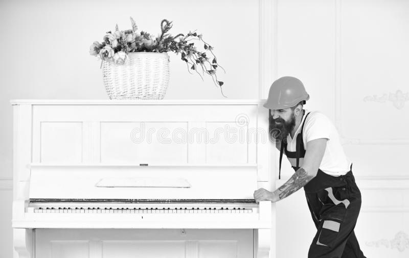 Smiling strong man with stylish beard and mustache trying to move old wooden piano with flower vase. Handsome worker in. Orange protective helmet on white stock photos