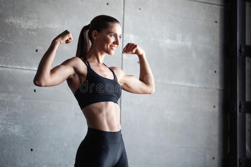 Smiling strong woman in black sportswear. stock photo