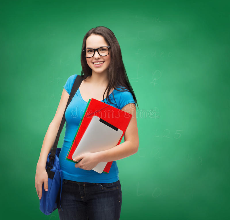 Smiling student with bag, folders and tablet pc. Education, technology and people concept - smiling student wearing black eyeglasses with bag, folders and tablet royalty free stock photos