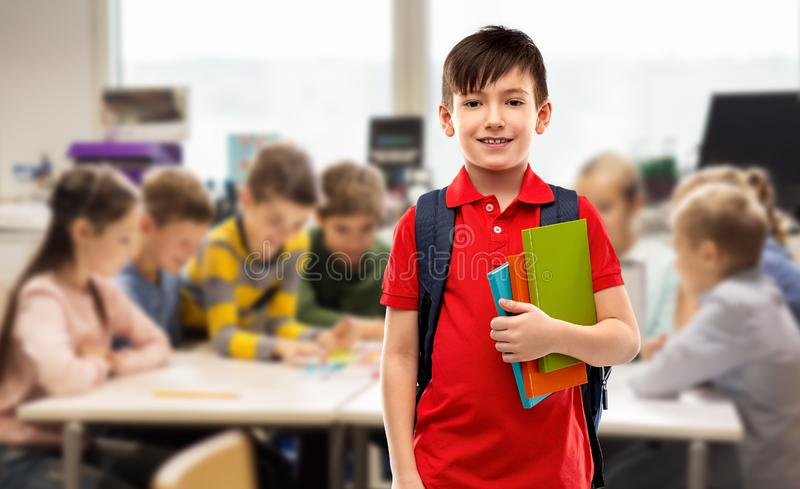 Smiling student boy with books and school bag royalty free stock image
