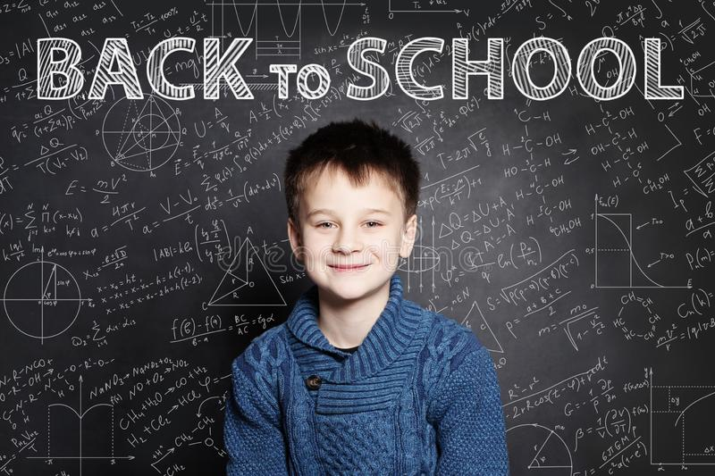Smiling Student child thinking on chalkboard with math formulas stock images