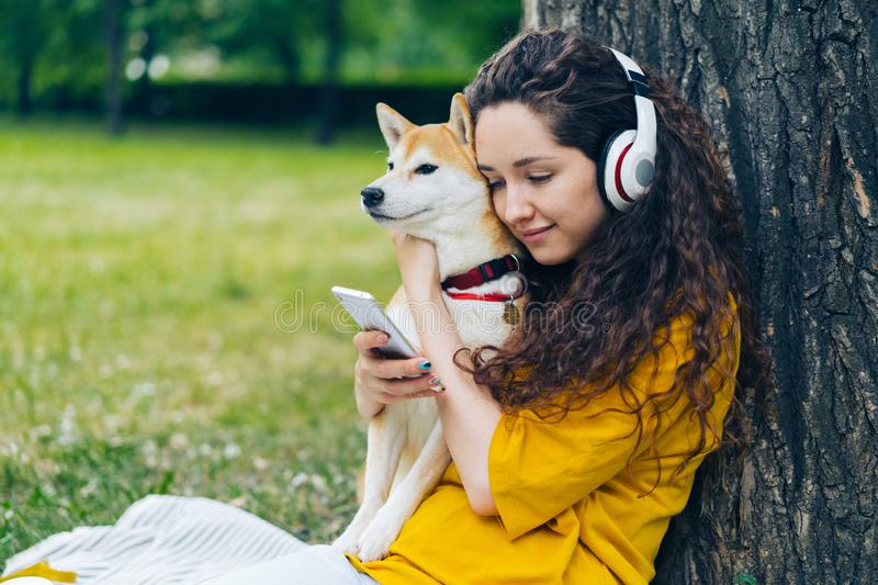 Smiling student enjoying music in headphones using smartphone in park with dog royalty free stock images
