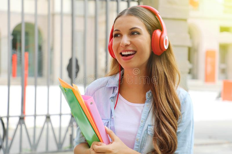 Smiling student girl with headphone and folders looking to the side outdoors.  stock image