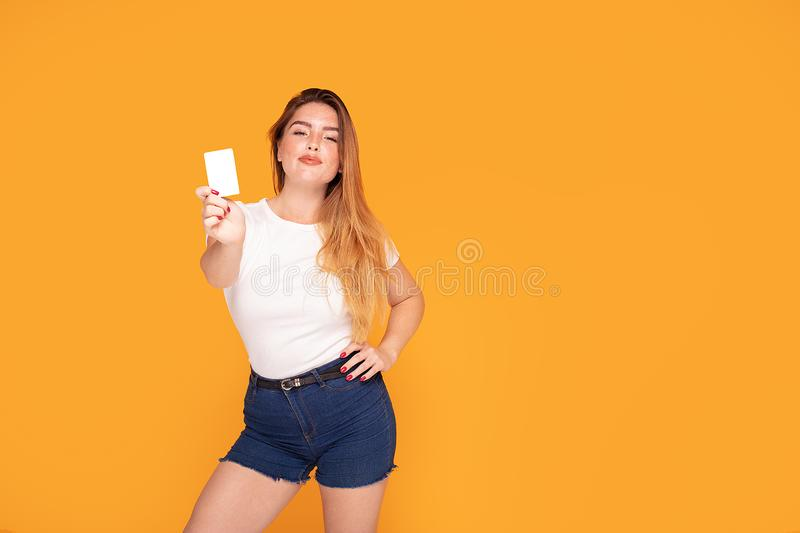 Smiling student girl holding credit card. Happy beautiful redhead woman holding credit card in hand, smiling, posing in studio stock images