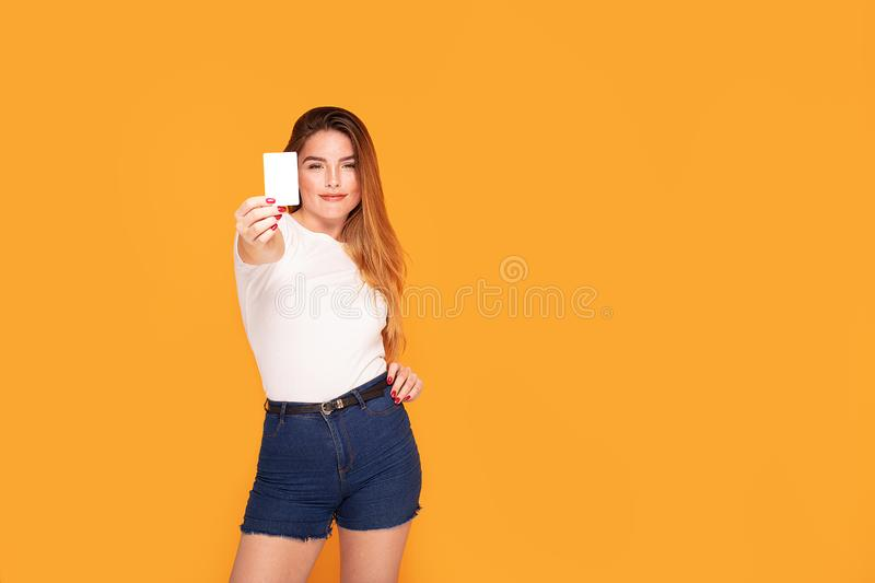 Smiling student girl holding credit card. Happy beautiful redhead woman holding credit card in hand, smiling, posing in studio stock photo