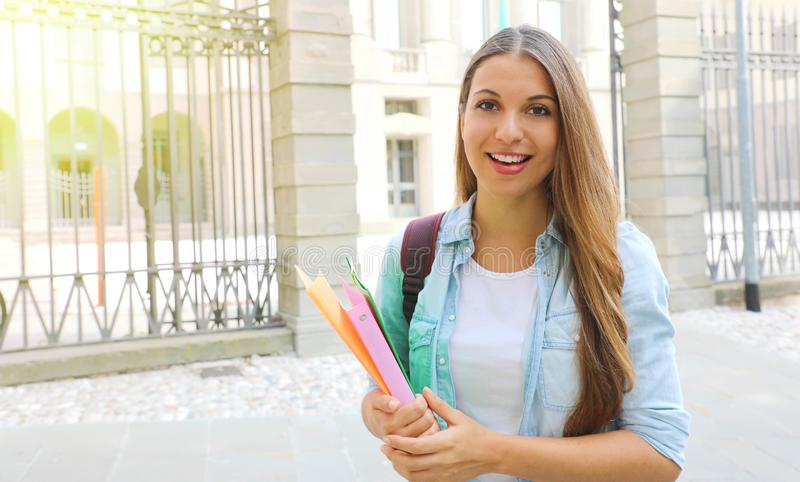 Smiling student girl holding folders with school on the background. Looks at camera. Copy space.  stock photos