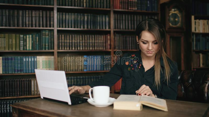 Smiling student girl working on laptop and read book in university library indoors royalty free stock image