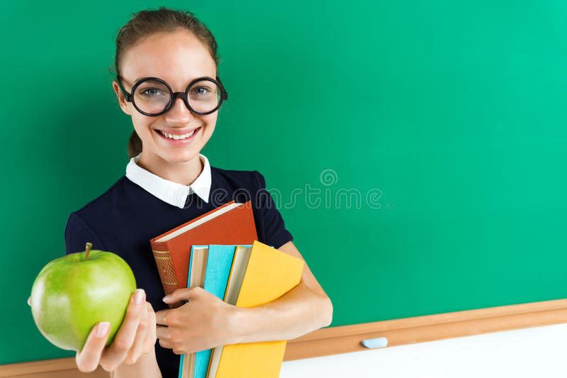 Smiling student hugging books and gives an apple. Photo of teen near blackboard, education concept stock photos