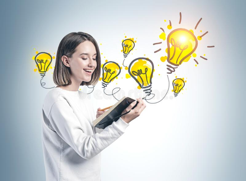Smiling student with notebook and her bright idea stock image