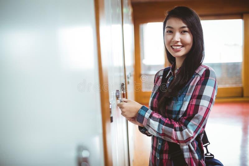 Smiling student opening locker stock photo