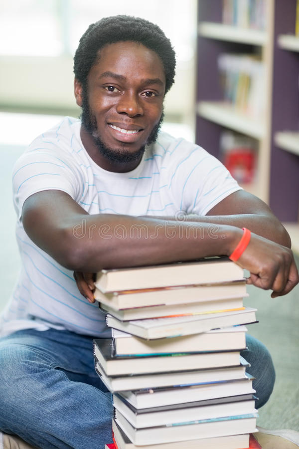 Smiling Student With Stacked Books Sitting In royalty free stock photos