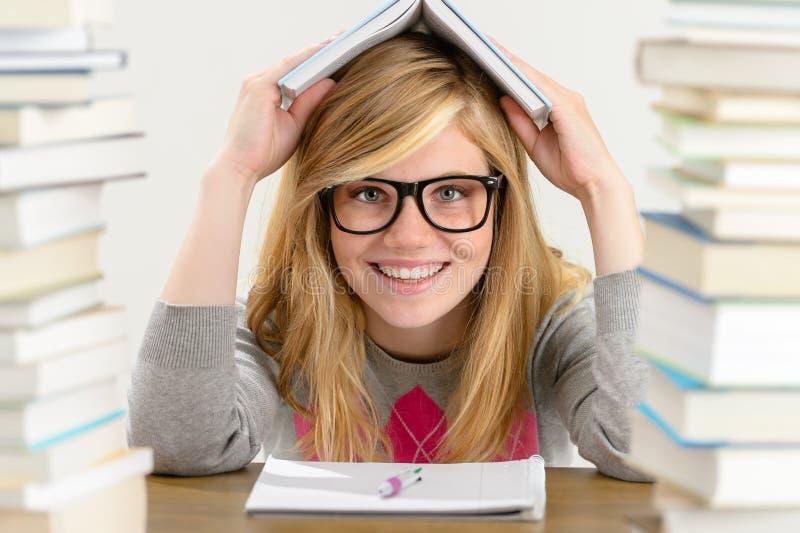 Smiling student teenager holding book over head. Smiling student teenager holding book over her head sitting desk stock image