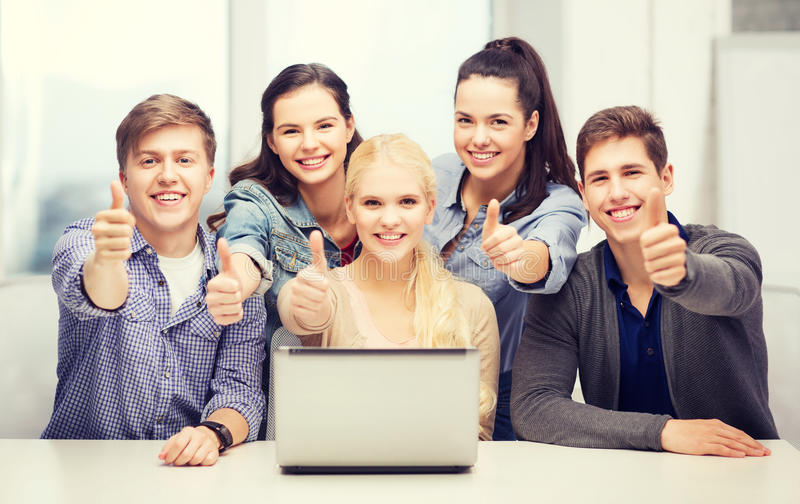 Smiling students with laptop showing thumbs up. Education, technology and internet concept - smiling students with laptop showing thumbs up at school royalty free stock images
