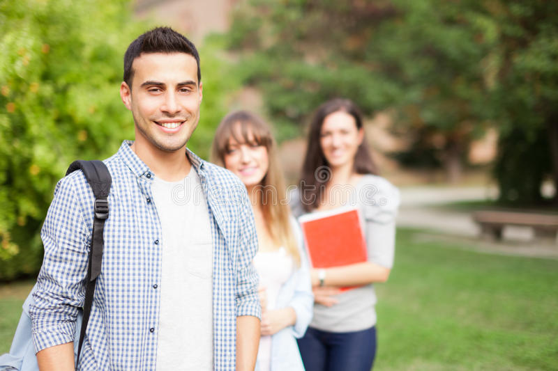 Smiling students in a park royalty free stock photos