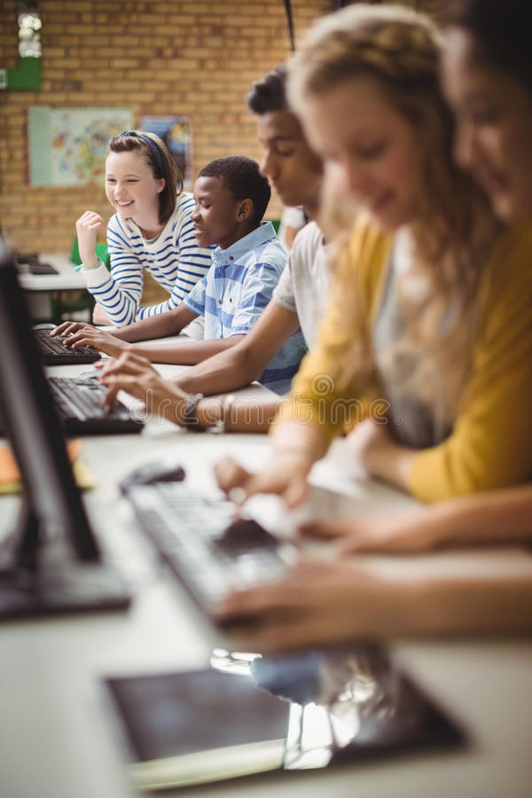 Smiling students studying in computer classroom stock image