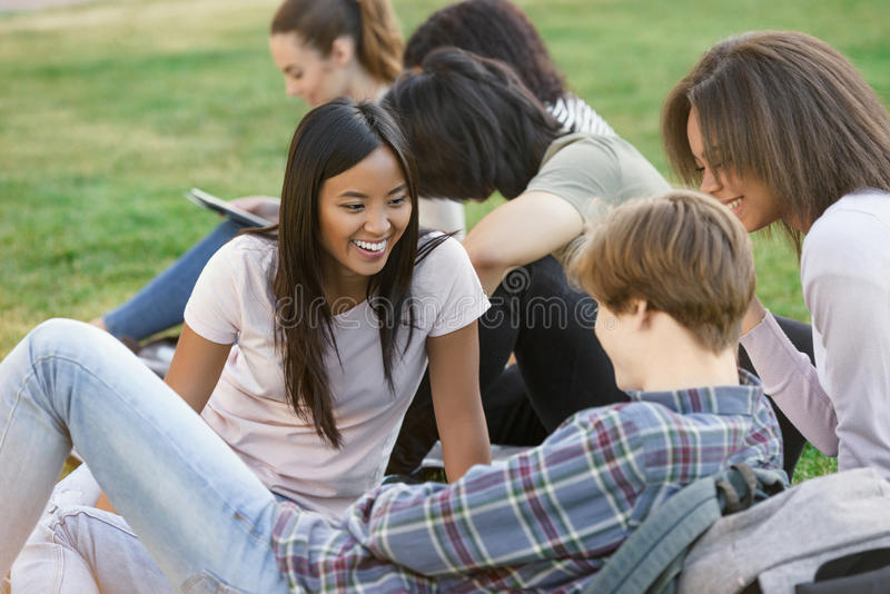 Smiling students studying outdoors. Looking aside. stock images