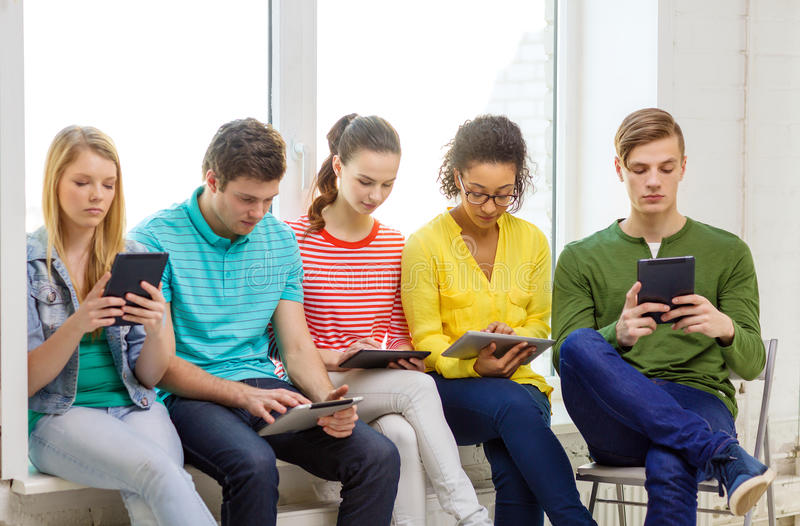 Smiling students with tablet pc computer. Education and technology concept - smiling students with tablet pc computer at school stock photo