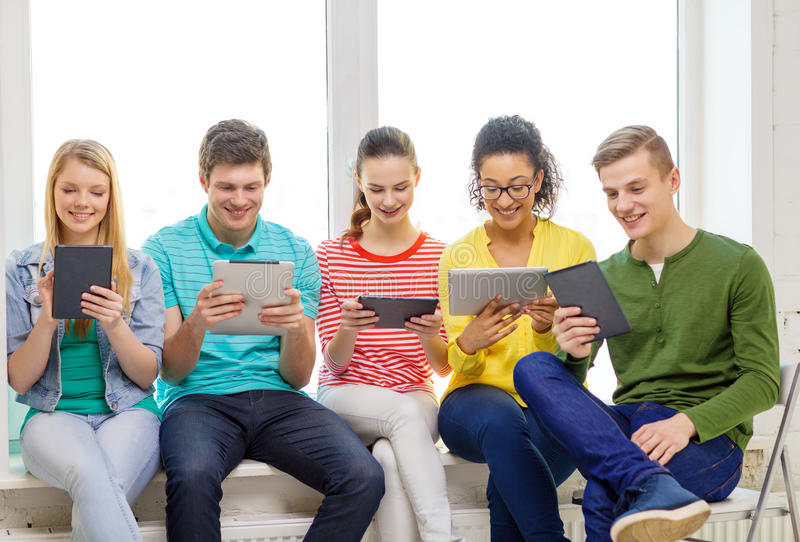 Smiling students with tablet pc computer. Education and technology concept - smiling students with tablet pc computer at school royalty free stock photos