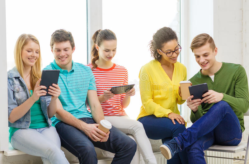 Smiling students with tablet pc computer. Education and technology concept - smiling students with tablet pc computer at school stock photography