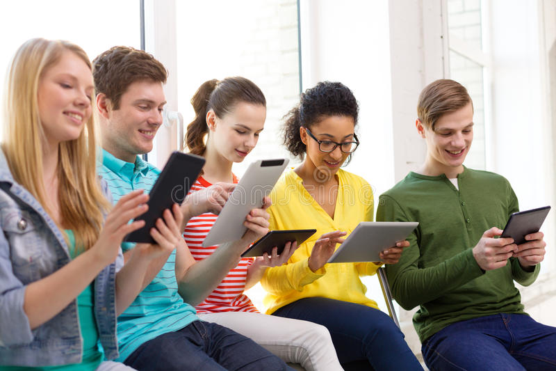 Smiling students with tablet pc at school stock photo