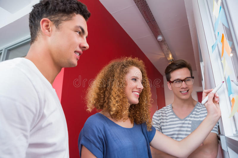 Smiling students working together on whiteboard stock photography