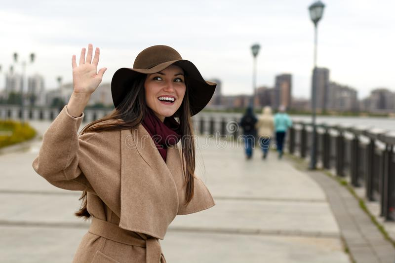 Smiling stylish girl in a coat with belt and big hat waving HELLO. The concept of welcome, friendliness, fun.  stock image
