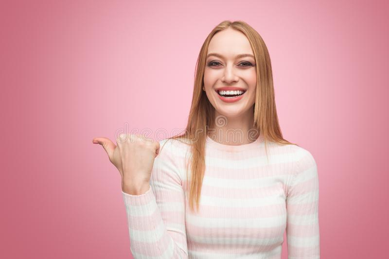 Smiling stylish model pointing away with finger royalty free stock images