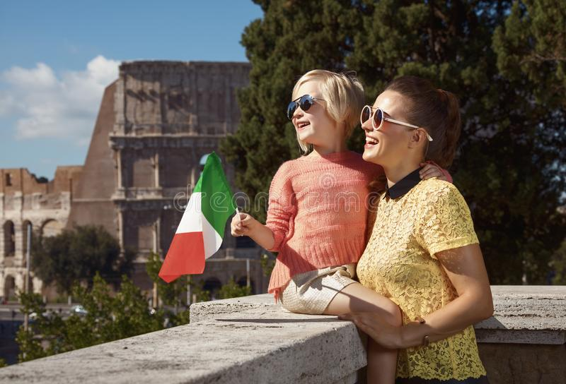 Smiling mother and daughter travellers with Italian flag. Smiling stylish mother and daughter travellers not far from Colosseum with Italian flag royalty free stock photography