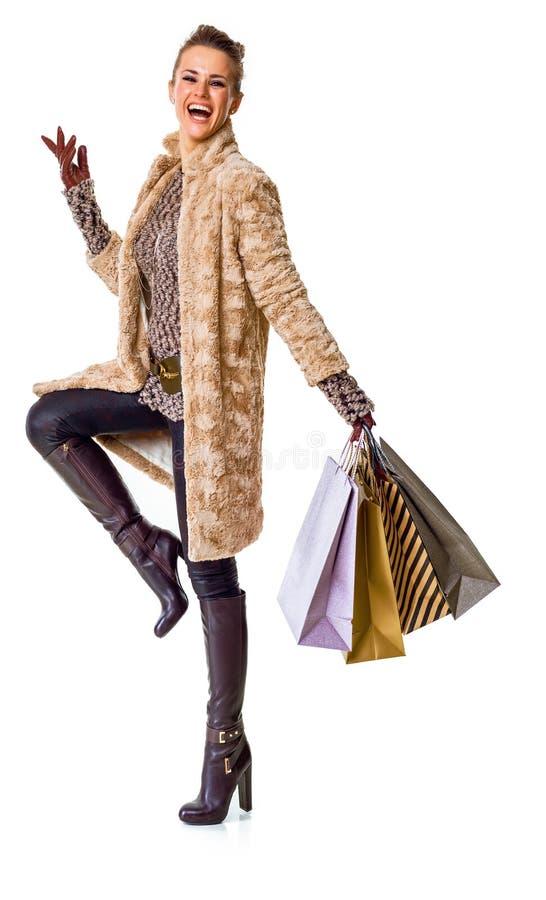 Smiling stylish shopper in winter coat on white background stock photos