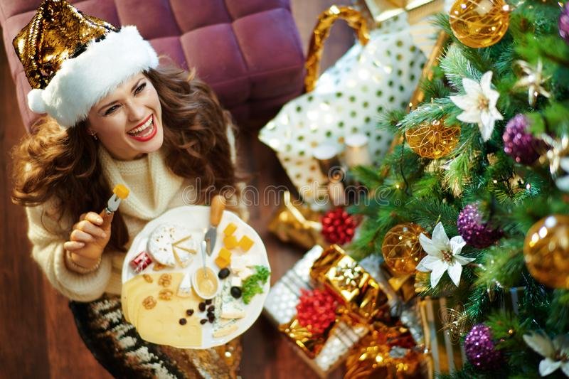 Smiling stylish woman eating cheese and holding plate royalty free stock images