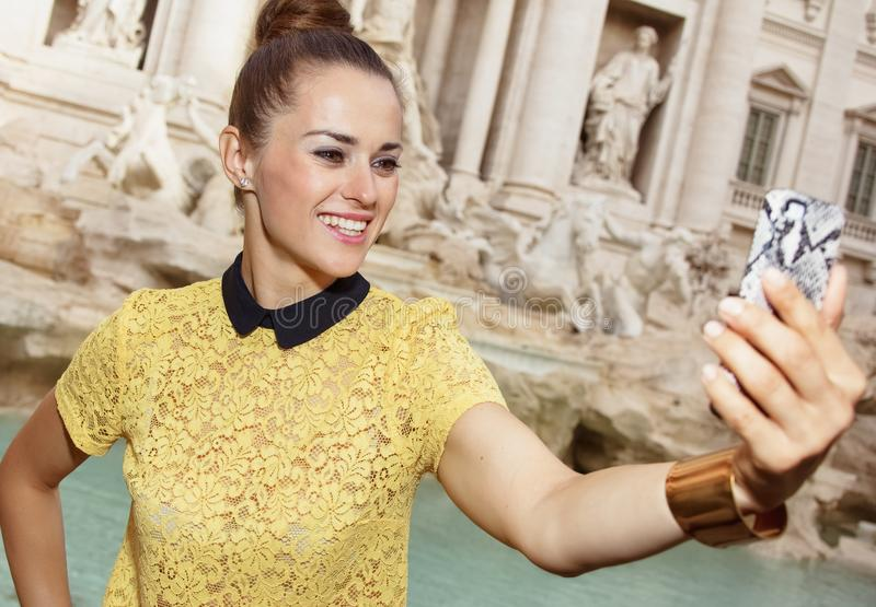 Smiling stylish woman in Rome, Italy taking selfie with phone. Smiling stylish woman in yellow blouse in Rome, Italy taking selfie with mobile phone royalty free stock photography