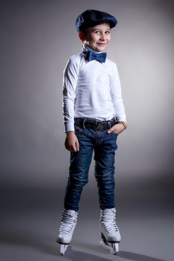 Smiling stylishly dressed boy posing in ice skates royalty free stock images